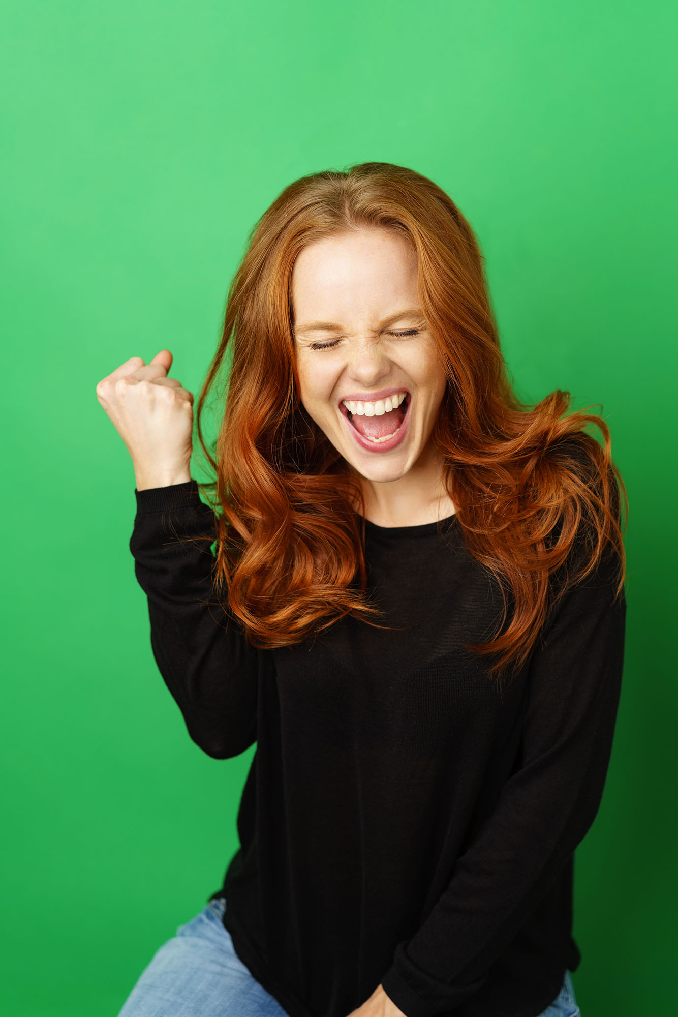 Jubilant excited young woman cheering and punching the air with her fist over a green studio background